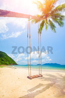 Beautiful tropical island beach with coconut palm trees and swing