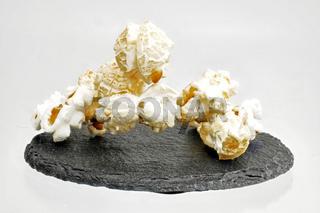 auf einer schwarzen Platte Popcorn gezuckert