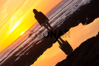 Woman on rocky beach watching sunset.