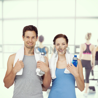 Composite image of portrait of a happy fit couple with water bottles
