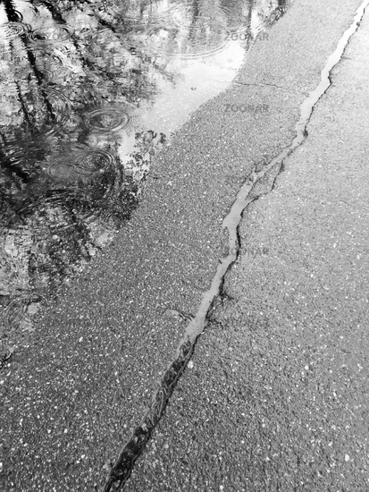 wet cracked asphalt surface with rain puddle