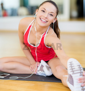 smiling girl with smartphone and earphones in gym