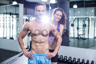 Smiling muscular couple looking at the camera