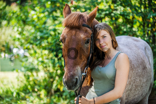smiling young woman close-up with horse