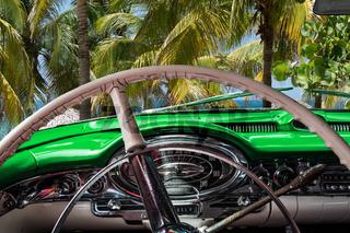 Kuba Innenansicht eines grünen Oldtimers mit Palmen und Blick auf das Meer