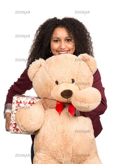 Frau hält Teddy und Weihnachtsgeschenk