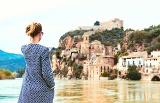 Woman traveller enjoying the view of the Miravet village and Ebro river. Spain