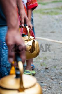 Queue of People with golden pot in hand