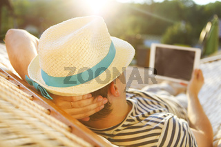 Man in hat in a hammock with tablet computer on a summer day