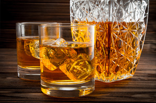 Closeup of bottle and two glasses with ice and whiskey