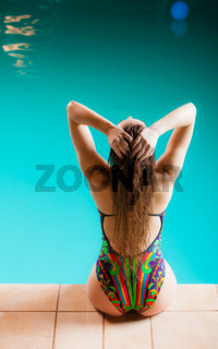 Woman back in swimsuit on pool edge.