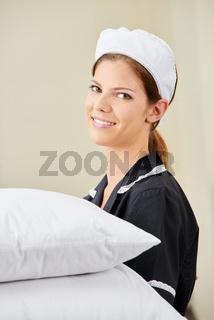 Zimmermädchen bringt frische Kopfkissen