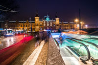 People, trams, escalator, Central Railway Station at night, Amsterdam, Netherlands