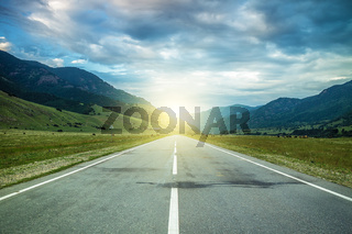 road in summer mountains to the sunset