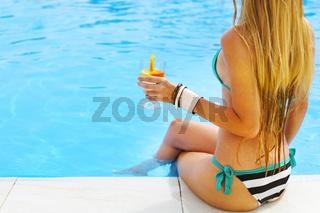 Pretty blond woman enjoying cocktail near the swimming pool