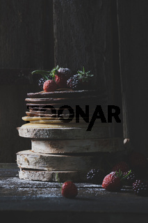 Breakfast in the wood : chocolate pancakes with strawberries, blackberries and castor sugar