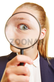 Frau schaut kritisch durch Lupe