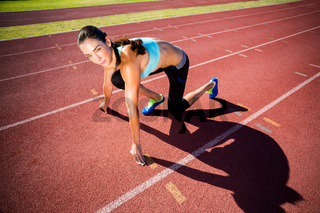 Portrait of female athlete in ready to run position