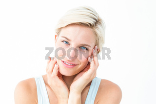Happy blonde smiling at camera with hands on cheeks