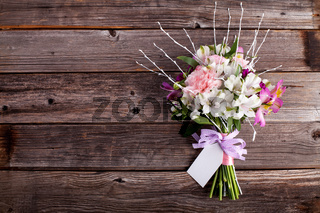 Pink bouquet from gillyflowers and alstroemeria on old wooden background with note