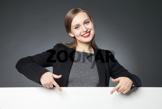 Smiling beautiful woman pointing at blank space