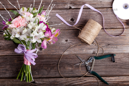 Father's Day bouquet from gillyflowers and alstroemeria on old wooden background with wooden heart and scissors