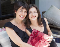 Mother and daughter with gifts sitting outdoors