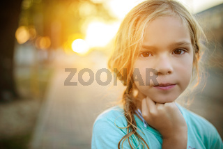Little girl on background of sunset on street