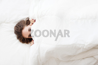 woman in bed under the blanket