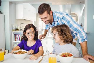 Happy man with children having breakfast