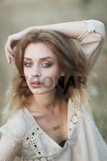 Young sexy model posing in a field at sunset