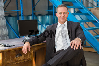 Smiling warehouse manage sitting with his legs crossed