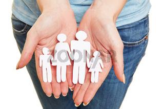Hände halten Familie aus Papier als Symbol