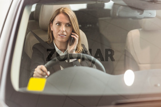 Smiling businesswoman having a phone call while sitting in a car
