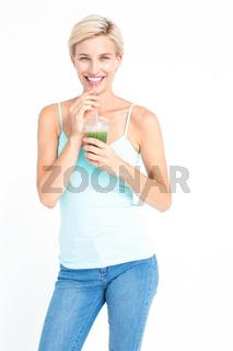 Beautiful woman drinking green juice