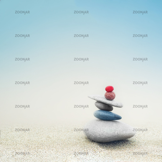 Balancing colorful zen stones pyramid on sandy beach under blue sky. Beautiful nature and spiritual concept