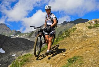 Weiblicher Mountainbike Fahrer auf einem steilen Trail, Schweiz