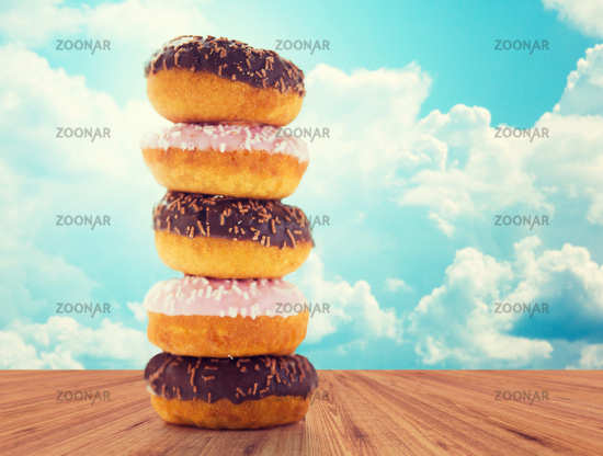 close up of glazed donuts pile over blue sky