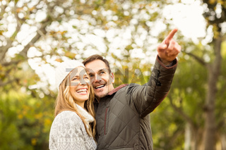 Portrait of smiling young couple pointing something