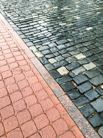 wet block sidewalk and rough cobblestone road