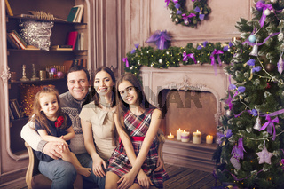 Stylish family celebrating christmas in room over christmas tree