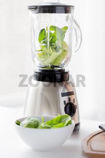 close up of blender jar and green vegetables
