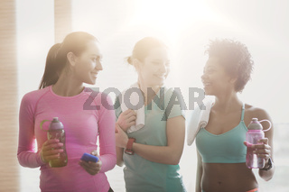 happy women with bottles of water in gym