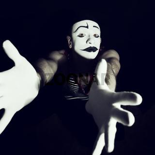 Sad mime on black background