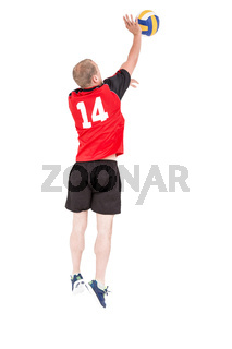 Rear view of sportsman hitting volleyball