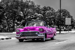 Pink farbener Oldtimer Cabriolet fährt auf dem Malecon in Kuba Havanna