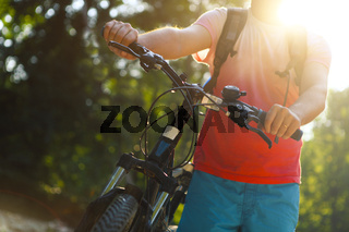 Young man with bicycle by mountain river