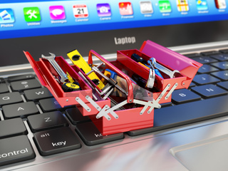 Laptop and toolbox with tools. Online support.