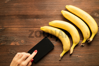 Female hand using a smartphone with a touch screen, near the bananas lie on a wooden table