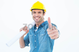 Architect holding blueprint while gesturing thumbs up